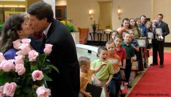 Michelle and Jim Bob Duggar, kiss after they and their 17 children, right, served as the honorary duck masters during the presentation of the d_117387
