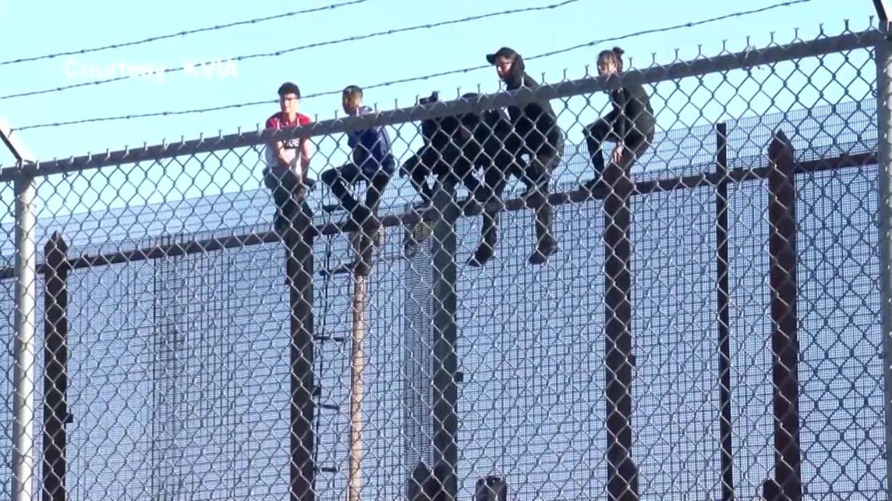 Undocumented immigrants scale border wall